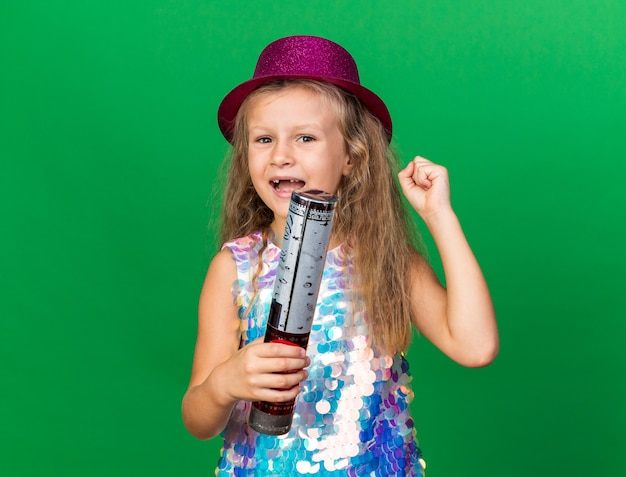 Joyful little blonde girl with purple party hat holding confetti cannon and keeping fist up isolated on green wall with copy space