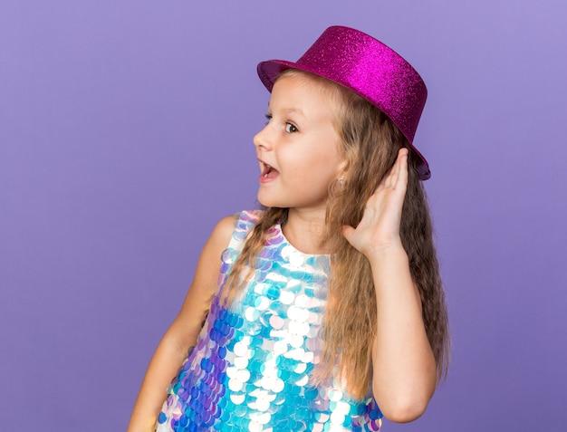 Gioiosa bimba bionda con cappello da festa viola che tiene la mano vicino all'orecchio cercando di sentire isolato sul muro viola con spazio copia