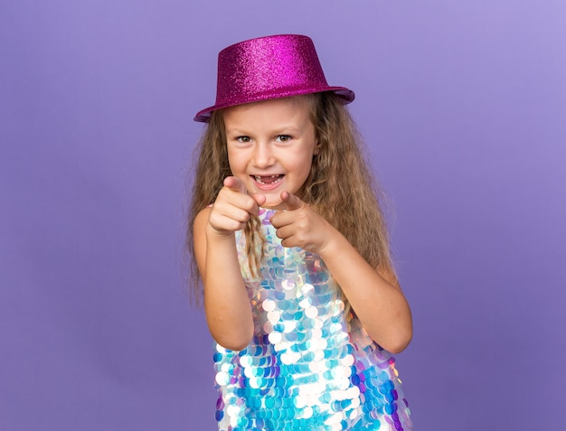 Gioiosa bambina bionda con cappello da festa viola che punta isolato sul muro viola con spazio per copia