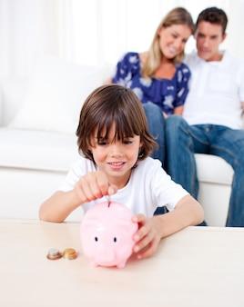 Радостный маленький мальчик, вставляющий монеты в копилку в гостиной