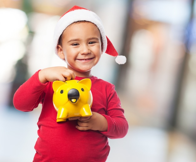 Joyful little boy with piggybank and santa claus hat
