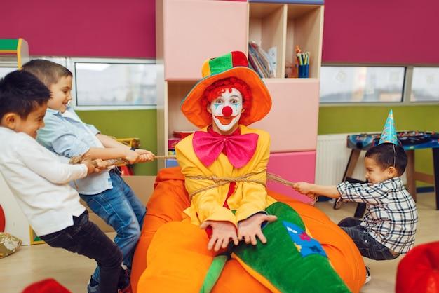 うれしそうな男の子は子供たちのエリアで面白いピエロを縛りました。プレイルームで祝う誕生日パーティー、