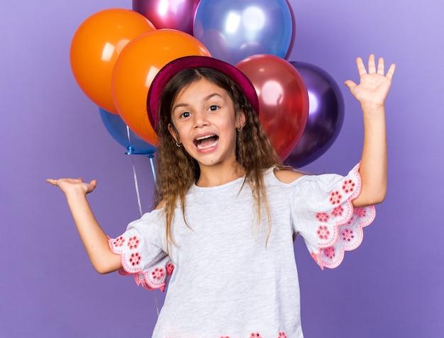 Gioiosa piccola ragazza caucasica con cappello da festa viola in piedi con le mani alzate davanti a palloncini di elio isolati sul muro viola con spazio di copia
