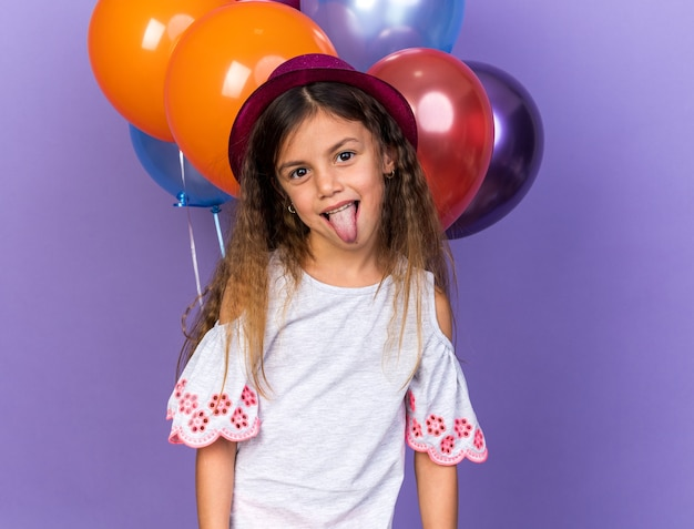 Joyful little caucasian girl with violet party hat stucks out tongue standing in front of helium balloons isolated on purple wall with copy space