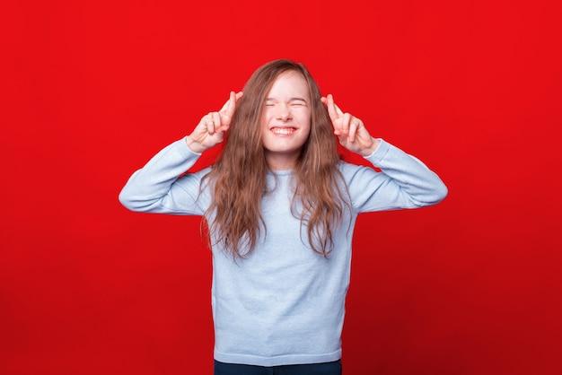 Радостная маленькая девочка скрещивает пальцы и загадывает желание над красной стеной
