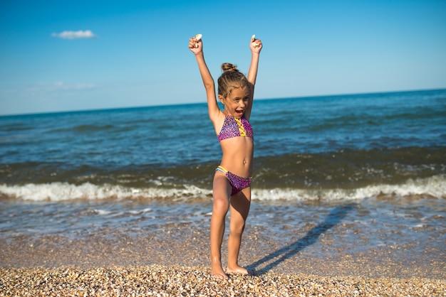 즐거운 어린 소녀는 화창한 따뜻한 여름날에 바다에서 휴식을 취하면서 해변의 날을 즐깁니다. 여름 휴가 및 휴식 개념
