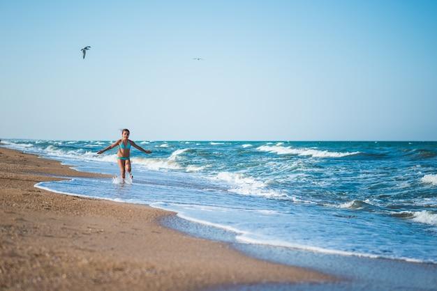 즐거운 어린 소녀는 화창한 따뜻한 여름날에 바다에서 휴식을 취하면서 해변의 날을 즐깁니다.
