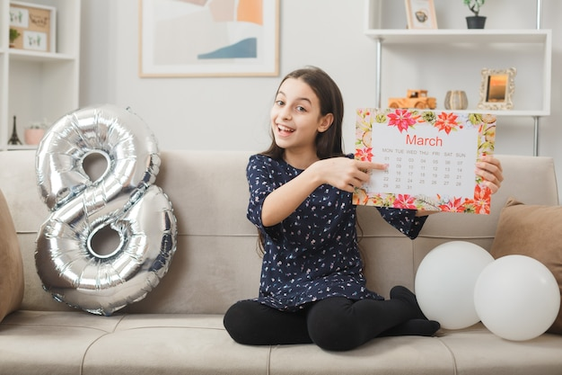 Joyful little girl on happy woman's day holding out postcard sitting on sofa in living room