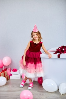Радостная маленькая девочка в розовом платье и кроссовках с большой подарочной коробкой и воздушными шарами