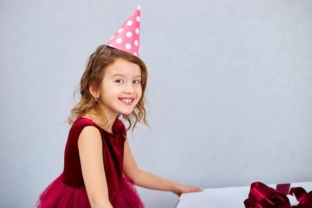 Радостная маленькая девочка в розовом платье и кроссовках с большой подарочной коробкой