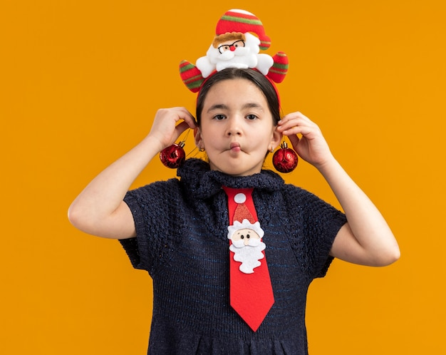 Joyful  little girl in knit dress wearing  red tie with funny rim on head holding christmas balls over her ears happy and positive making grimace standing over orange wall