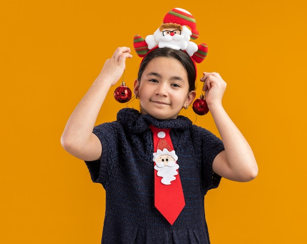 Joyful  little girl in knit dress wearing  red tie with funny rim on head holding christmas balls over her ears  smiling standing over orange wall