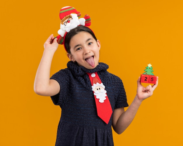 Joyful little girl in knit dress wearing red tie with funny rim on head holding toy cubes with christmas date sticking out tongue