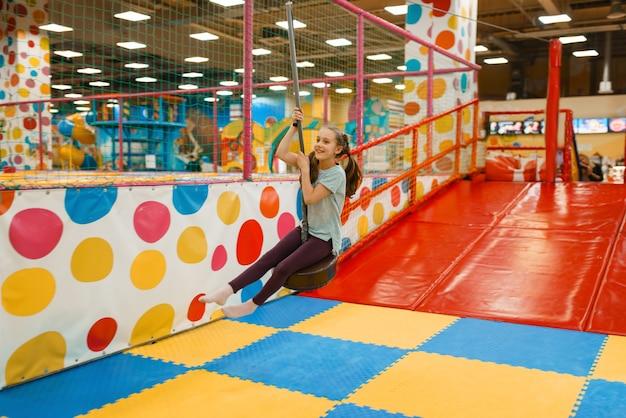 Радостная маленькая девочка катается на качелях в развлекательном центре. отдых девочек в праздники, детское счастье, счастливые дети на детской площадке