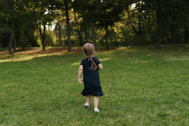 Радостная маленькая девочка на зеленой траве