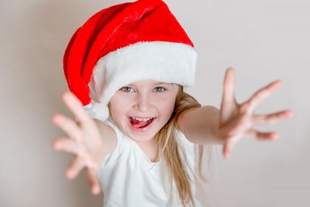 Joyful little girl in santa's hat smiles and