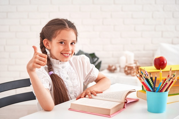 Joyful little girl sitting at the table with pencils