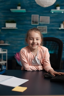 Радостная маленькая девочка улыбается, сидя за партой для онлайн-школы