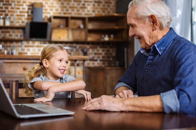 Радостная маленькая девочка улыбается во время разговора с дедушкой на кухне