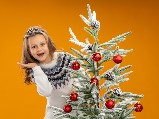 Joyful little girl standing behind christmas tree wearing tiara with garland on neck spreading hand isolated on orange background