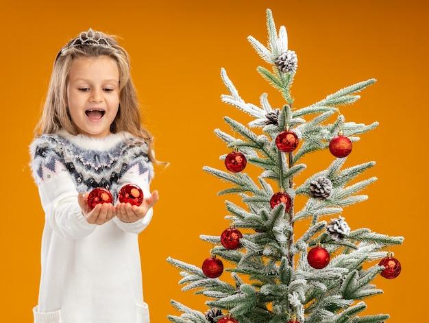 Bambina allegra che sta vicino all'albero di natale che indossa la tiara con la ghirlanda sul collo che tiene fuori le palle di natale alla macchina fotografica isolata su fondo arancio