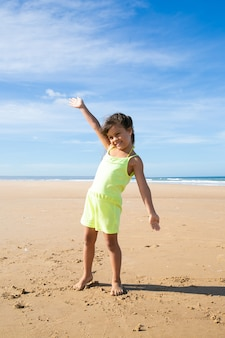 Joyful little girl in summer cloth enjoying activities on beach at sea, dancing with open arms on golden sand, looking away