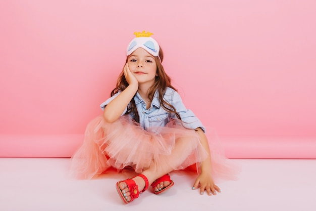 Joyful little girl in tulle skirt sitting on white floor isolated on pink background. pretty princess child with mask on head smiling to camera, expressing happiness of pretty kid