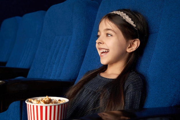 Joyful little girl watching movie, laughing in cinema.