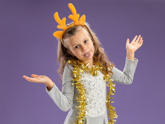 Joyful little girl wearing christmas hair hoop with garland on neck spreading hands and showing tongue isolated on blue background