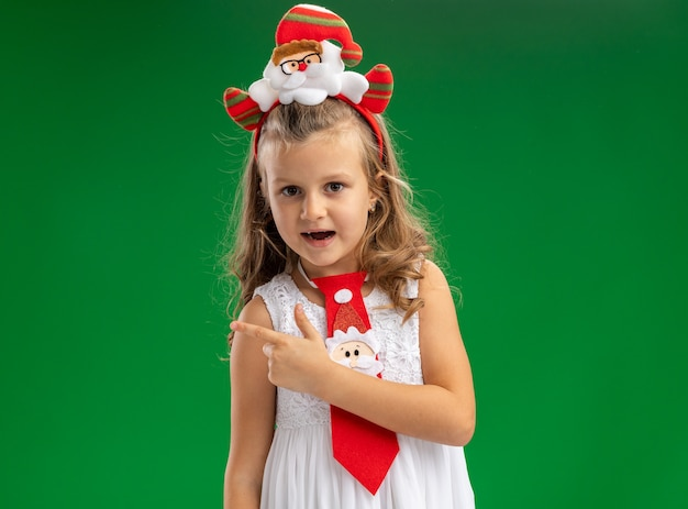 Joyful little girl wearing christmas hair hoop with tie points at side isolated on green background