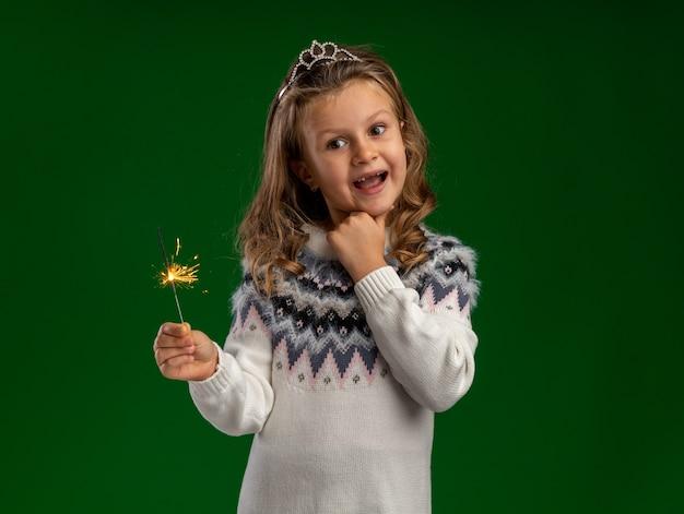 Gioiosa bambina indossa tiara tenendo le stelle filanti ha afferrato il mento isolato su sfondo verde