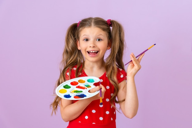 A joyful little girl with a paint palette and a brush on a purple background.