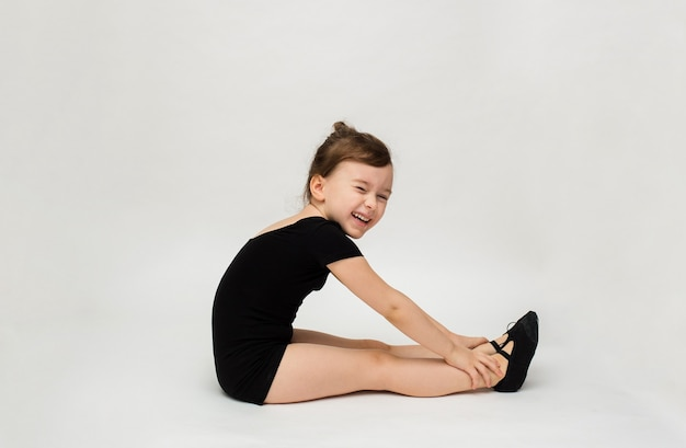 Joyful little gymnast girl sits sideways and does a stretch on a white background