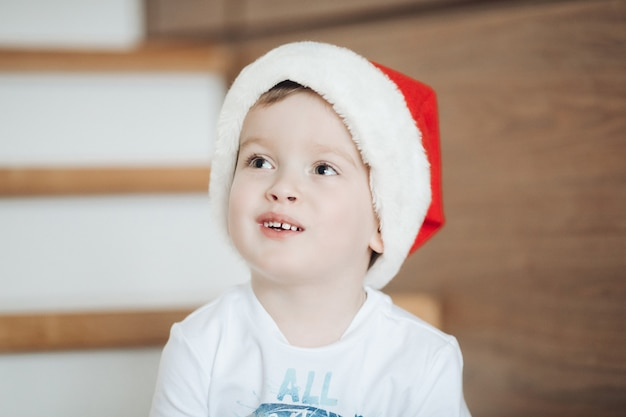Joyful little kid keeping smile on his face while being on christmas photo session