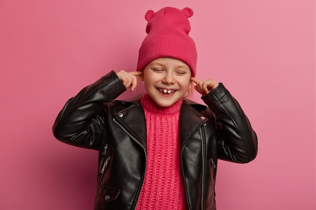 Joyful little preschooler covers ears, keeps index fingers in ear holes, avoids hearing loud music, has happy expression, wears pink hat with ears and leather jacket, doesnt want to hear noise