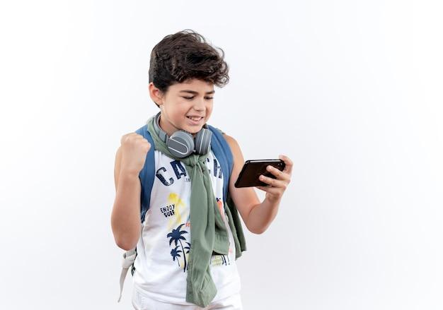 バックパックとヘッドフォンを身に着けているうれしそうな小さな男子生徒が電話で遊んで、はいジェスチャーを示しています