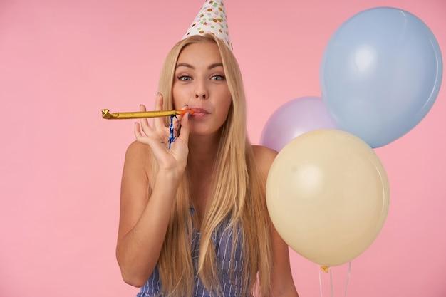 Gioiosa donna bionda dai capelli lunghi in abito estivo blu e cappello di compleanno che tiene un mazzo di palloncini di elio, guardando la telecamera allegramente e soffiando corno di partito, isolato su sfondo rosa