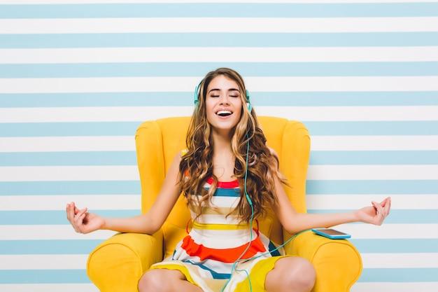 Радостная длинноволосая девушка медитирует, сидя в позе лотоса на синей полосатой стене. довольно молодая женщина в красочном платье охлаждает в желтом кресле и слушает расслабляющую музыку.
