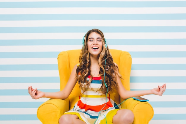 Joyful long-haired girl meditating while sitting in a lotus pose on blue striped wall. pretty young woman in colorful dress chilling in yellow armchair and listening relaxing music.