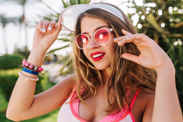 Joyful long-haired girl in trendy white hat and bright bracelets looking with interest and posing, waving her hands