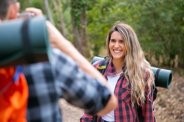 그녀의 자른 남자 친구가 카메라로 사진을 찍을 때 포즈를 취하고 웃고있는 즐거운 장발 여자. 자연에 함께 여행하는 행복 등산객. 배낭 여행, 모험, 여름 휴가 개념