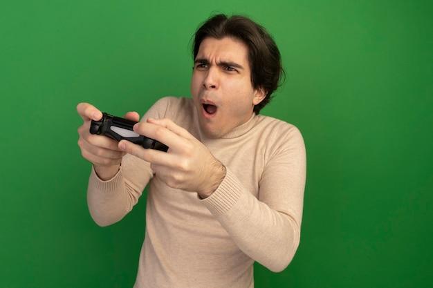 Радостный глядя на сторону молодого красивого парня, держащего джойстик игрового контроллера, изолированного на зеленой стене