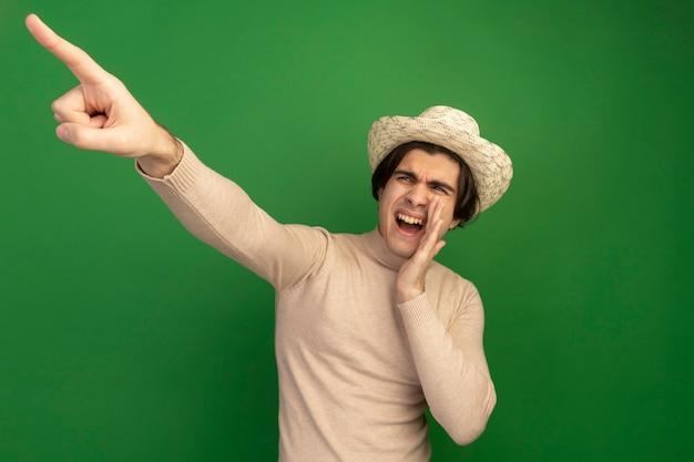 Радостный глядя в сторону молодой красивый парень в шляпе, зовущий кого-то указывает на сторону, изолированную на зеленой стене