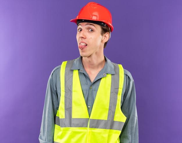 Joyful looking at camera young builder man in uniform showing tongue