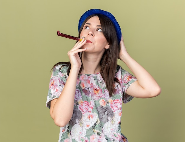 Gioiosa giovane bella ragazza che indossa il cappello da festa che soffia il fischio della festa mettendo la mano sulla testa