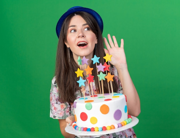 Joyful looking side young beautiful girl wearing party hat holding cake showing hello gesture isolated on green wall