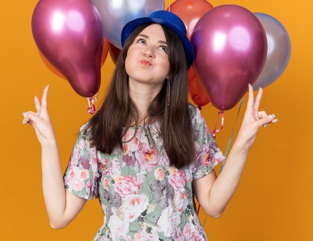 オレンジ色の壁に分離された平和のジェスチャーを示す前の風船に立っているパーティーハットを身に着けている若い美しい少女をうれしそうに見上げる
