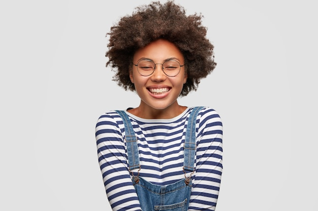 Joyful lovely dark skinned female with pleased expression, has broad smile, closes eyes in happiness, wears fashionable overalls, expresses positive emotions, isolated over white wall.