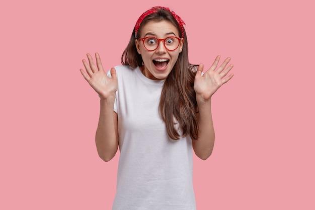 Радостная милая девушка веселится, активно жестикулирует, смеется над чем-то смешным, носит красную повязку на голову и повседневную футболку, показывает ладони на камеру