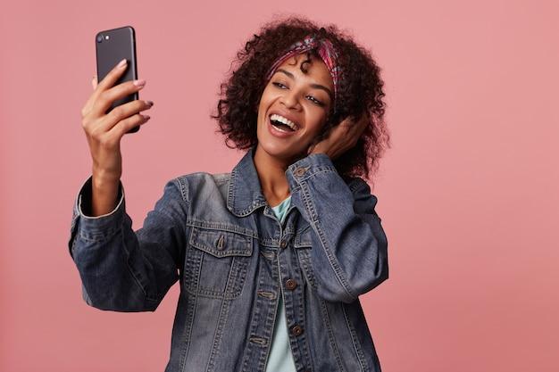 Радостная милая улыбающаяся темнокожая кудрявая брюнетка с короткой стрижкой и красочной повязкой на голове, позируя, поднимая руку с мобильным телефоном, фотографируя себя